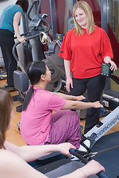 Fitness instructor showing two women how to use the rowing machine at their sports leisure centre,