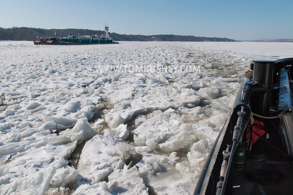 The United States Coast Guard cutter Sturgeon Bay breaks ice in the shipping channel on the Hudson River near Hudson, New York. The Eva Leigh Cutler, an oil tank barge, is at left,