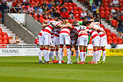 Doncaster Rovers players huddle during the EFL Sky Bet League 1 match between Doncaster Rovers and Gillingham at the Keepmoat Stadium, Doncaster, England on 3 August 2019.