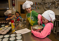Cameron Drouin with Aiden Stafford and Charlotte Lehr with Alexandra Fay mixing up their batter for chocolate chip banana muffins during cooking class at the Gilford Youth Center Tuesday afternoon.  (Karen Bobotas/for the Laconia Daily Sun)