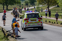 © Licensed to London News Pictures. 26/04/2020. London, UK. A Police car patrols Richmond Park. Members of the public go out to enjoy the warm weather in Richmond Park which looked busy today during lockdown where temperatures are expected to reach 21c. London has seen an increase in traffic and busier High Streets as more shops and cafes start to open up during the coronavirus pandemic crisis. Photo credit: Alex Lentati/LNP