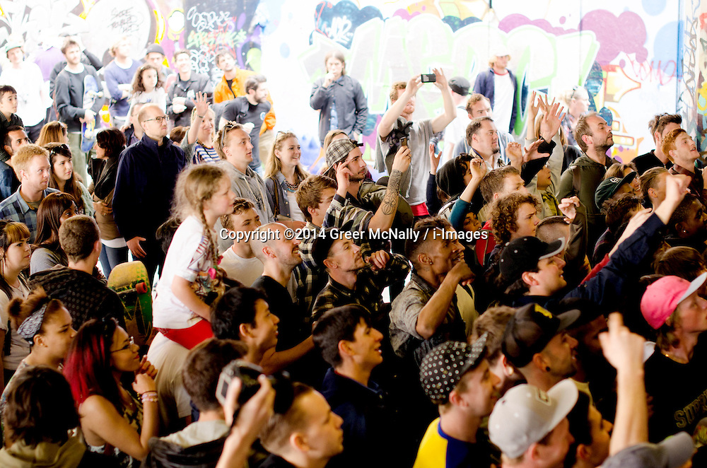 A little girl sits on her father's shoulders hoping to catch one of the many goodies being thrown into the crowd at the Long Live Southbank event on the May bank holiday