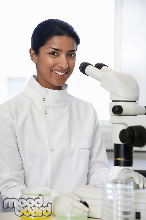 Female Asian lab worker standing by microscope