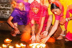 A close up of women beneath colorful saris sending lit candles with flowers      down the Ganges River from a step of the main Dasaswamedh Ghat in Varanasi, Varanasi, Uttar Pradesh, India