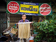 "29 DECEMBER 2018 - BANGKOK, THAILAND: A man carries longevity noodles out of the shophouse to drying racks in front of his home. The family has been making traditional ""mee sua"" noodles, also called ""longevity noodles"" for three generations in their home in central Bangkok. They use a recipe brought to Thailand from China. Longevity noodles are thought to contribute to a long and healthy life and  are served on special occasions, especially Chinese New Year, which is February 4, 2019. These noodles were being made for Chinese New Year.        PHOTO BY JACK KURTZ"