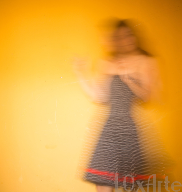 Carefree young woman in white spotted black dress with red ribbon dancing in front of a hot yellow background.