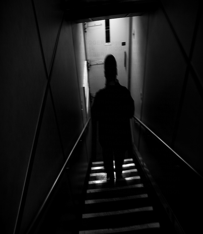 Silhouette of male figure walking down narrow unlit stairs in building
