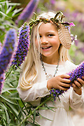 Laughing blond girl in rural chic forest fashion clothing in a forest setting with flowers.