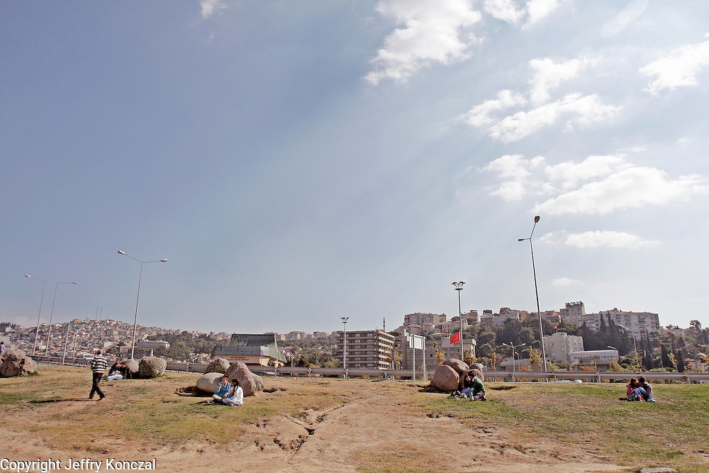 Couples sit along a grassy area in Izmir, Turkey.