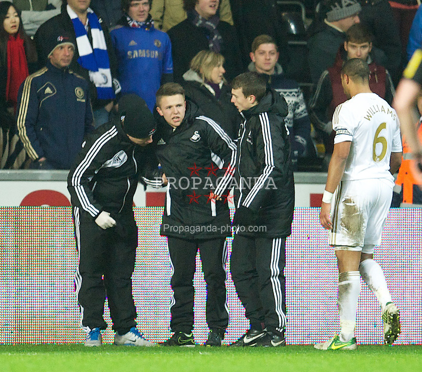 SWANSEA, WALES - Wednesday, January 23, 2013: Swansea City ball-boy Charlie Morgan is helped to his feet after being kicked by Chelsea's Eden Hazard during the Football League Cup Semi-Final 2nd Leg match at the Liberty Stadium. (Pic by David Rawcliffe/Propaganda)