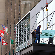Workmen installing large glass panels in hotel, Montreal, Quebec, Canada