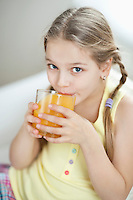 Portrait of little girl drinking orange juice