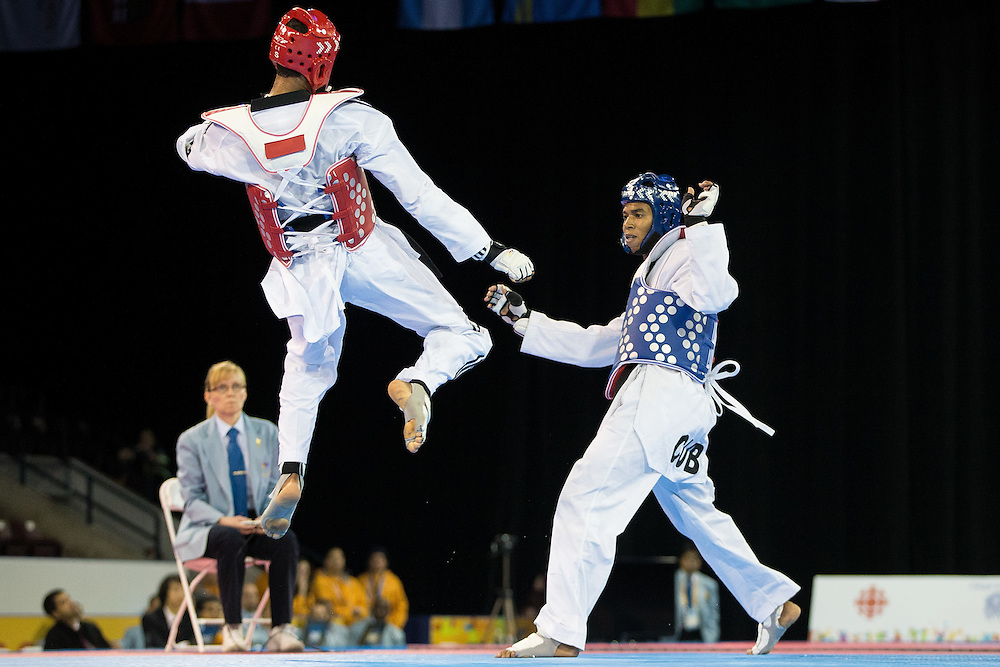 Moises Hernandez (L) of the Dominican Republic gets airborne to kick Jose Cobas of Cuba in their gold medal contest in men's taekwondo -80 kg division at the 2015 Pan American Games in Toronto, Canada, July 21,  2015.  AFP PHOTO/GEOFF ROBINS