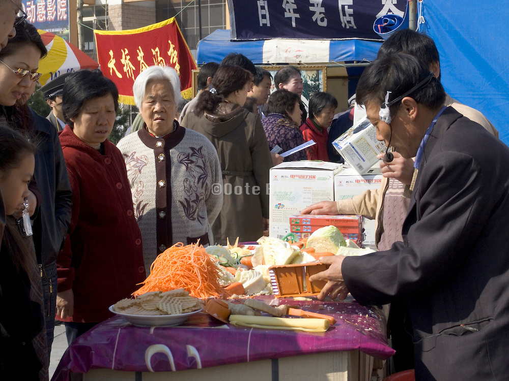 person demonstrating his product at an outdoor market China Beijing