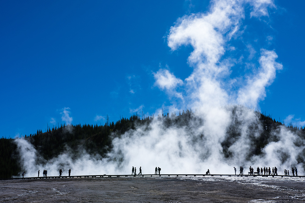 The Grand Prismatic spring of Yellowstone National Park, is the largest hot spring in the United States with over a million visitors every year, here you can see the silhouettes of tourists on the boardwalk against the rising steam of the spring.