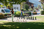 Playing a chess in the park with a man size chess board Zell am Ziller, Tyrol, Austria