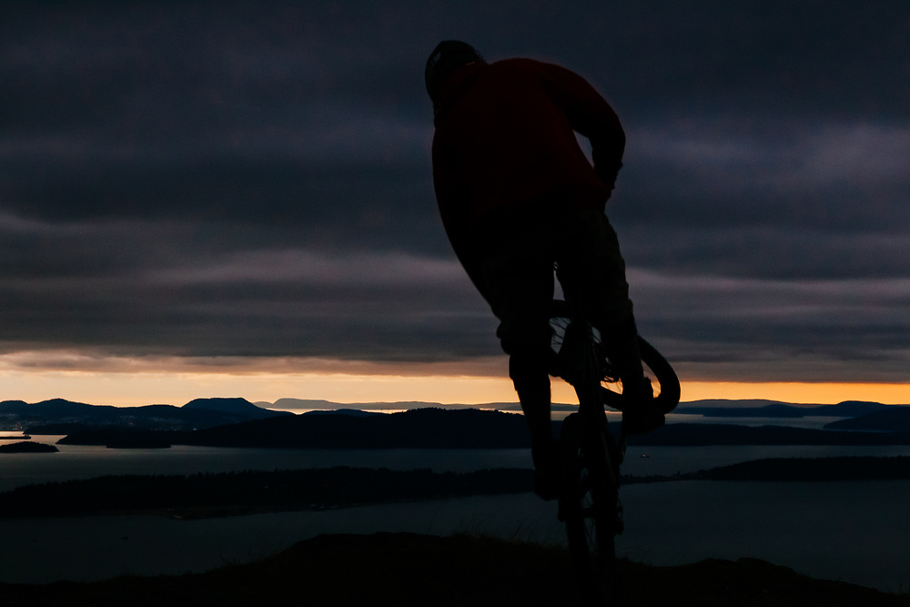 Owen Dudley exits the forest for the sea on a coastal mountain bike trail near Bellingham Washington.