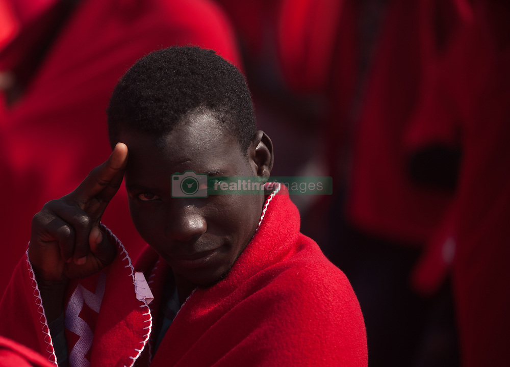April 26, 2018 - Malaga, Spain - A migrant covered by red blanket greets the camera while on board of a Spanish coast guard vessel. A group of migrants rescued from a dinghy in the Mediterranean Sea arrived at the Port of Málaga. Aboard from a boat, members of the Spanish Maritime Safety rescue a total of 80 migrants near the Malaga coast, wich 6 of them are women and 4 childs. (Credit Image: © Jesus Merida/SOPA Images via ZUMA Wire)