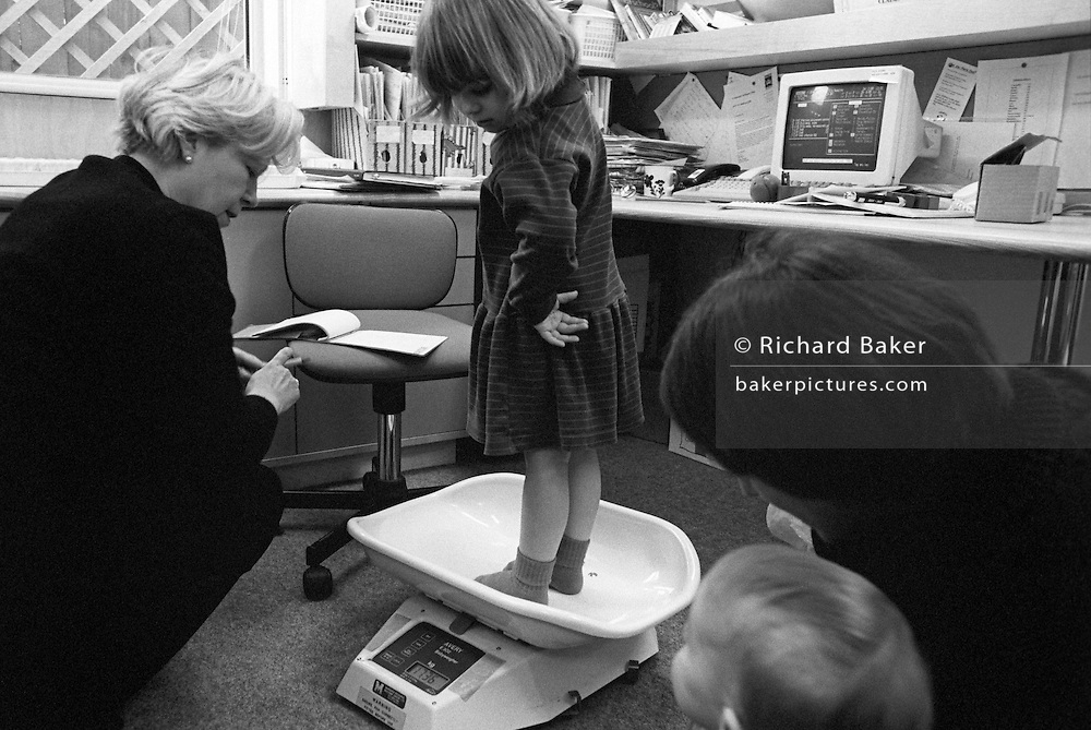 As a mother and younger brother look on, a 4 year-old girl has her weight checked by a local health visitor on scales in a south London childrens' clinic.