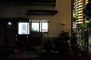 from inside lighted up window of a old residential house next to large flat complex Japan