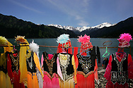 "Uygur ethnic minority costumes await customers, lined up at an improvised photo stand set by vendors at  Heavenly Lake in Xinjiang autonomous region, China Wednesday July 26. 2006. The stunning small deep blue lake at the feet of the 5445 meter Peak of God is a two hour and half drive from Urumqi, the capital of Xinjiang. ""China, the United Nations and neighboring Central Asian countries plan a program aimed at reviving the ancient Silk Road by boosting investment, trade and tourism. The two-year Silk Road Project involves the governments of China, Kazakhstan, Kyrgyzstan, Tajikistan and Uzbekistan. Winding more than 9,600 kilometers (6,000 miles) through desolate mountains and deserts, the Silk Road guided camel caravans to and from Central Asia and Europe. Marco Polo, Genghis Khan and Alexander the Great followed its paths."""
