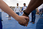 07 AUGUST 2005 - PHOENIX, AZ: Members of the Agape Harvest Church gather for prayer on a street corner in Phoenix, AZ, Sunday, Aug. 7, before setting up tents for a church service for homeless people. Agape Harvest Church holds weekly church services for street people in Phoenix. They also hand out water and food and distribute clothes. They have been involved in the street ministry for about six months.  PHOTO BY JACK KURTZ