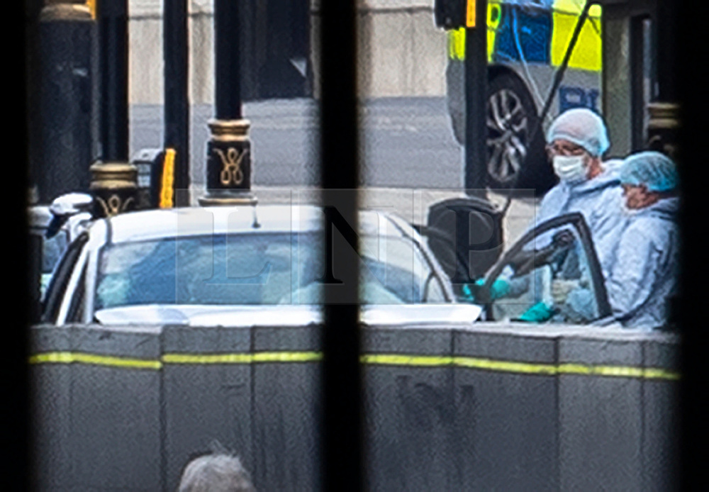 © Licensed to London News Pictures. 14/08/2018. London, UK. Police in forensics suits examine the damaged silver car that crashed into barriers outside Parliament. A number of pedestrians are injured. The driver has been arrested.  Photo credit: Peter Macdiarmid/LNP