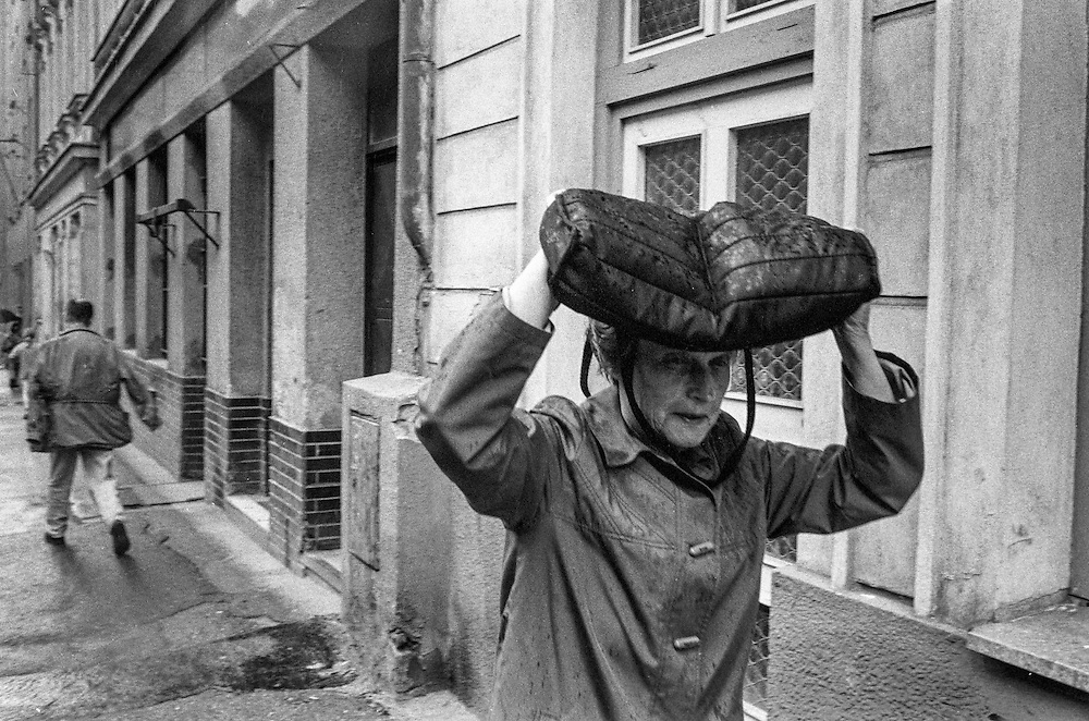 A woman covering her head during a rainy day in the streets of Zizkov.