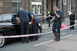 © Licensed to London News Pictures. 25/07/2017. LONDON, UK.  Police officers examine a car at the crime scene cordon on Burnham Street just off Roman Street this evening near Singh supermarket.  Two males in their late teens have been taken to hospital for treatment after an unknown liquid was thrown at them. Photo credit: Vickie Flores/LNP