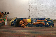 A young girl sleep in a house. .Hundreds of families displaced by the war and not more able to pay a rent found shelter in the buildings not completely demolished in Bab Al Aziziya, the Kaddafi stronghold and symbol of the regime in center Tripoli.