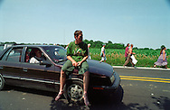 Copyright ©Ê2004 Jeremy Hogan - All Rights Reserved..A deadhead rides barefoot on the hood of a car to Grateful Dead show at Deercreek, Indiana during July 1995. Other walk down the road along a cornfield. ..Generation x, genx, grateful dead, deadhead, deadheads, dropout, hippy, hipster, hip, traveler, youth culture, journey, Americana, 90s, 1990s, counterculture,