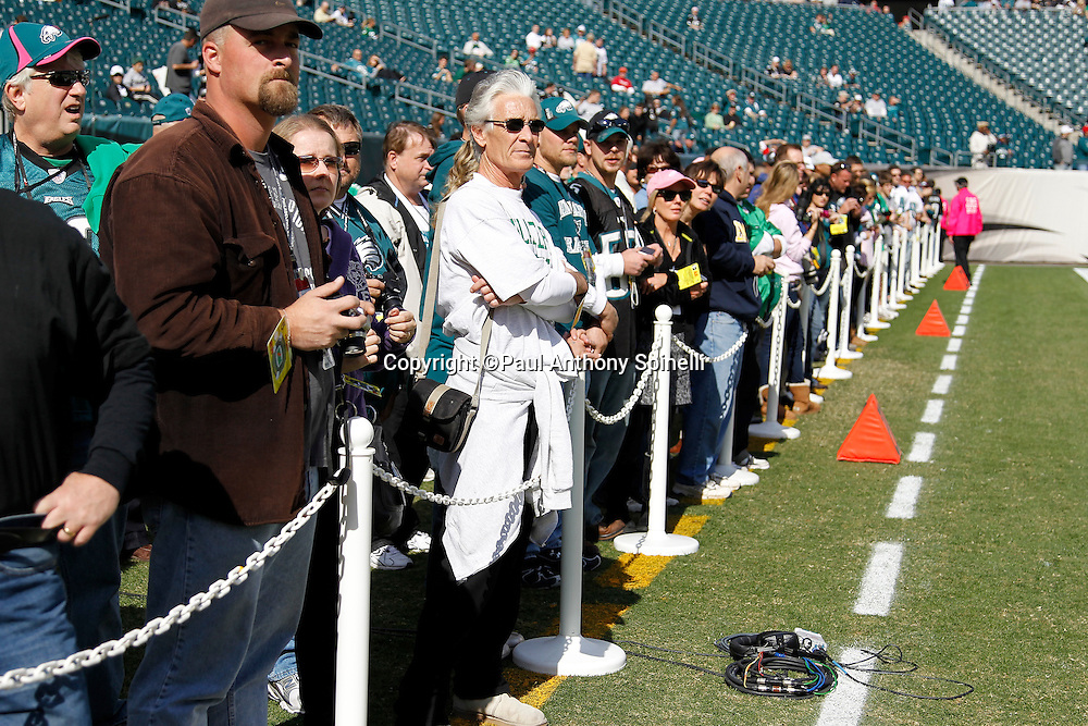 VIP fans watch pregame warmups while standing on the sidelines at the Philadelphia Eagles NFL week 6 football game against the Atlanta Falcons on Sunday, October 17, 2010 in Philadelphia, Pennsylvania. The Eagles won the game 31-17. (©Paul Anthony Spinelli)