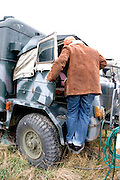 Man climbing into a military truck at the site of a mock up of a military mess hall in Poland where soup and bread is served.  Rawa Mazowiecka  Central Poland