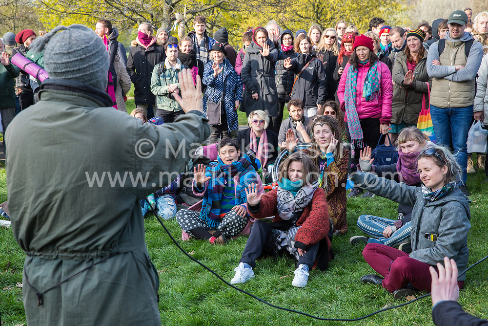 London, UK. 14th April 2019. Storm Granny teaches deescalation techniques to climate campaigners from Extinction Rebellion gathered in Hyde Park following the Earth March in preparation for 'International Rebellion UK - Shut Down London!' events next week to call on the Government to take urgent action to address climate change.
