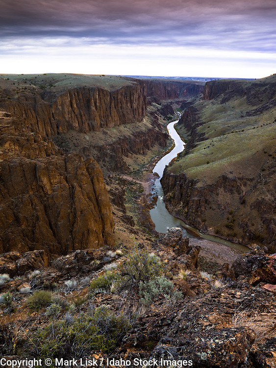 A silvery ribon of water cuts throught lava cliffs on the South Fork of the Owyhee River.