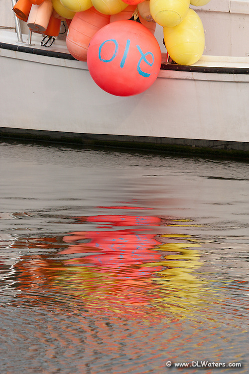 Buoys and reflection on a fishing trawler in Wancheese harbor.
