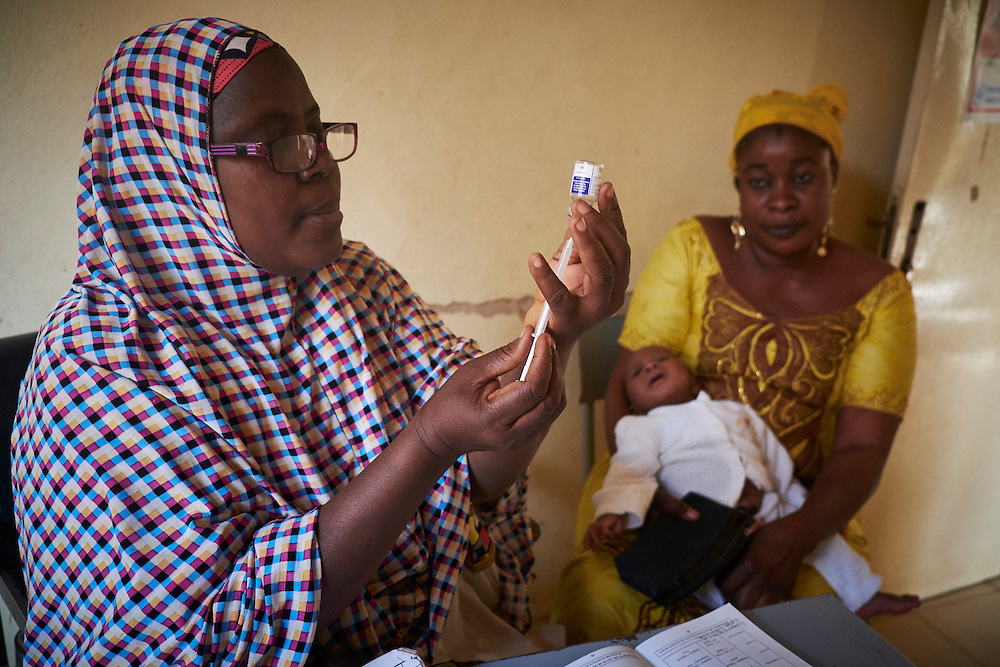 Nurse Amadou Aissatou prepares a vaccination before administering it to baby Mohamed, 3 weeks old held by his mother Zoubeirou Mariana, 33 years at the Banga Bana health centre, Niamey, Niger on February 16, 2016.