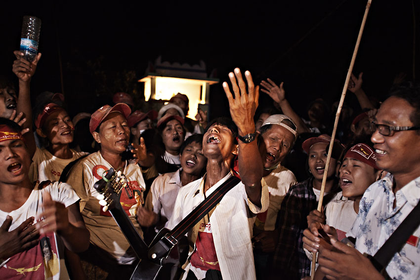 NLD supporters gathered to sing and celebrate their leader Daw Aung San Suu Kyi outside her house as she arrived in Wah Thin Kah village to spend the night before the by-election of April 1st 2012. Kawhmu township, Yangon, Myanmr.