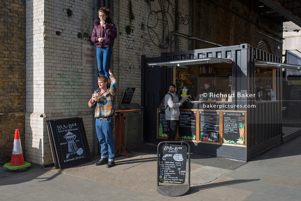 An female acrobat spontaneously stands on the shoulders of a friend at a coffee kiosk, on 2nd March 2017, in The Cut, London borough of Southwark, England.