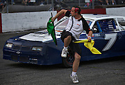 Race flagman taps his backside while signalling to a driver during a re-start at Agassiz Speedway in Agassiz, BC (2012)
