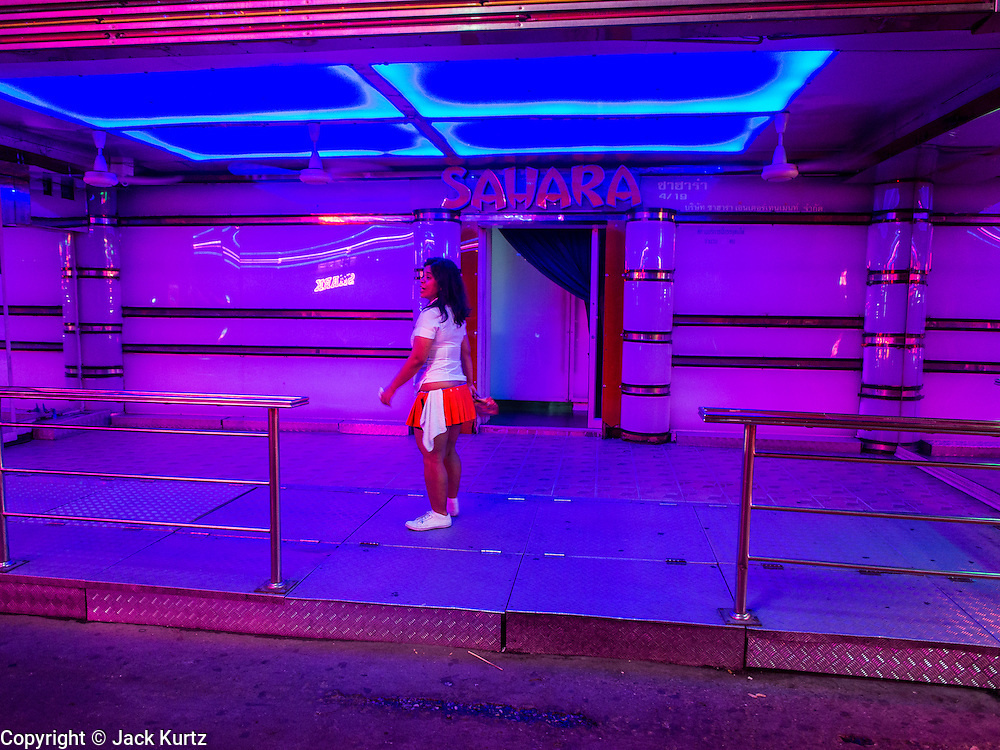 "22 MAY 2014 - BANGKOK, THAILAND:   A waitress in a bar on Soi Cowboy, one of Bangkok's ""adult entertainment"" districts, closes her bar after the army announced an overnight curfew. The Thai army suspended civilian rule, suspended the constitution and declared the ""military takeover of the nation."" The announcement came just before evening as a meeting between civilian politicians and the army was breaking up with no progress towards resolving the country's political impasse. Civilian politicians were arrested when the meeting ended. The army also declared a curfew from 10PM until 5AM.   PHOTO BY JACK KURTZ"