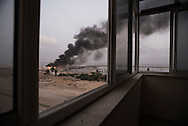 Gaza Strip, Gaza City: Plumes of smoke rise from facilities inside the port of Gaza City after was hit dawn by several Israeli strike on July 29, 2014. ALESSIO ROMENZI