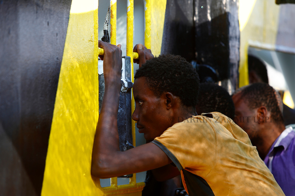A migrant looks out of a window on the Medecins san Frontiere (MSF) rescue ship Bourbon Argos as it arrives in Trapani, on the island of Sicily, Italy, August 9, 2015.  Some 241 mostly West African migrants on the ship arrived on the Italian island of Sicily on Sunday morning, according to MSF.<br /> REUTERS/Darrin Zammit Lupi <br /> MALTA OUT. NO COMMERCIAL OR EDITORIAL SALES IN MALTA
