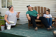 PRICE CHAMBERS / NEWS&amp;GUIDE<br /> Tamara and Dee J. Rammell relax on their deck with son Eli before cooking dinner on August 19.