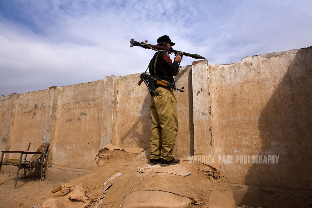 MATTANI, PAKISTAN - OCTOBER 27: A Pakistani Frontier Corps soldier stands on the roof of a fortification, monitoring the tribal border 30km outside Peshawar, on October 27, 2008, in Mattani, Pakistan. Since former president Musharraf's dismissal of the chief justice in early 2007, Pakistan has rapidly declined into chaos as pro-Taliban militants took advantage of the government's weaken position by stepping up attacks on government and military targets, taking control of large swaths of land, and implementing Sharia law. Pakistan suffers nearly daily attacks by militants seeking to extend their rule, destabilize the government and spread fear amongst the populace. As political infighting continues within the Pakistani leadership, authorities seem all but powerless in their fight against the militants. The US continues to denounce Pakistan ISI (Inter Services Intelligence) complacency and complicity with the Taliban, while operate unilaterally with drone attacks against targets of opportunity throughout the tribal and border region. US President Barack Obama authorized the deployment of more than 17,000 more troops to Afghanistan in an attempt to combat the Taliban resurgence. (Photo by Warrick Page)