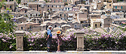 Tourists taking souvenir photographs using traditional camera in ancient city of Modica Alta famous for Baroque architecture,Sicily