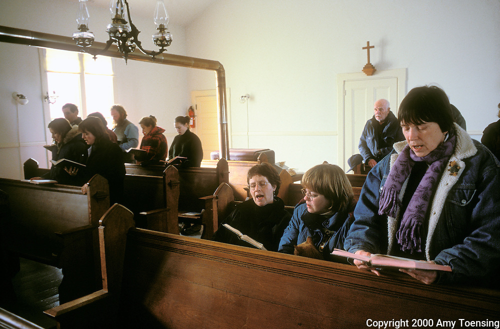 MONHEGAN ISLAND, MAINE - FEBRUARY 06: Residents and island visitors sing hymns during a Sunday service February 6, 2000 on Monhegan Island, Maine. The island only has one church. Monhegan Island, home to lobstermen and painters and a popular destination for tourists is twelve miles off the coast of Maine. Ringed by high, dark cliffs, its interior a mix of meadows, marsh and spruce groves, Monhegan is one of just 14 true island communities left off the coast of Maine. The island has a 65 permanent, year-round residents and the population grows to around 200 in the summer, with day-trippers adding several hundred more. (Photo by Amy Toensing) _________________________________________<br />