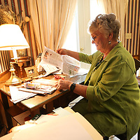 Louise Jones sits at her desk going through the obituaries to cut them out for lamanitation.
