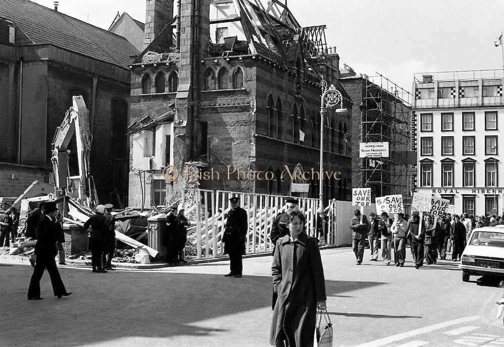 Building workers parade to save their jobs outside the half-demolished Molesworth Hall, while inside architectural students have staged a sit in to 'Save our Street'.<br /> 05/04/1978