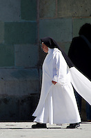 A Dominican nun walks past the Catedral de Oaxaca.